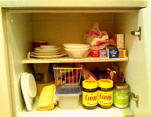 2段に分かれており、上段に食器とラップ類、下段に食料品と調理器具が雑多に収納されている。