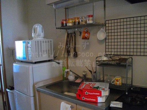 模様替え前のキッチン。ニトリの2段水切りが場所をとっている。スポンジがシンクに直置きされている。まな板を掛けるのにちょうどいいフックがなく、無理やり掛けられている。