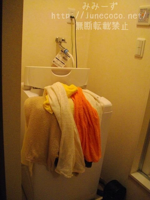 洗濯機のふちに山のように積まれたタオル(10枚はある)