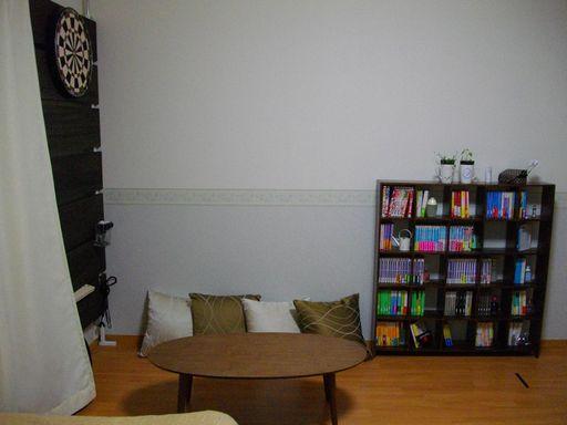 ベッド側から薄い本棚がある側の壁を望んだところ。壁際にクッションが4つあり、ベッドとの間にローテーブルが置かれている。