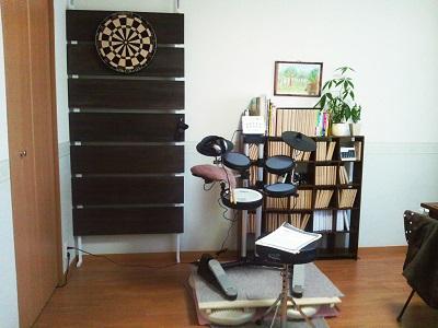 向かって左側には本棚とダーツボード、そして電子ドラムがある