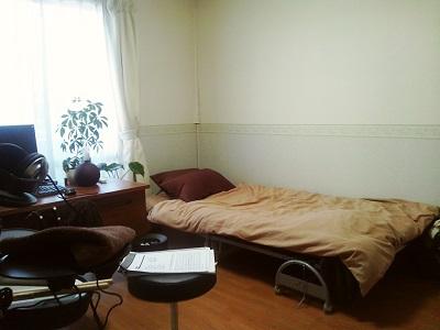 右側にはベッド。茶系のファブリックがかかっている。